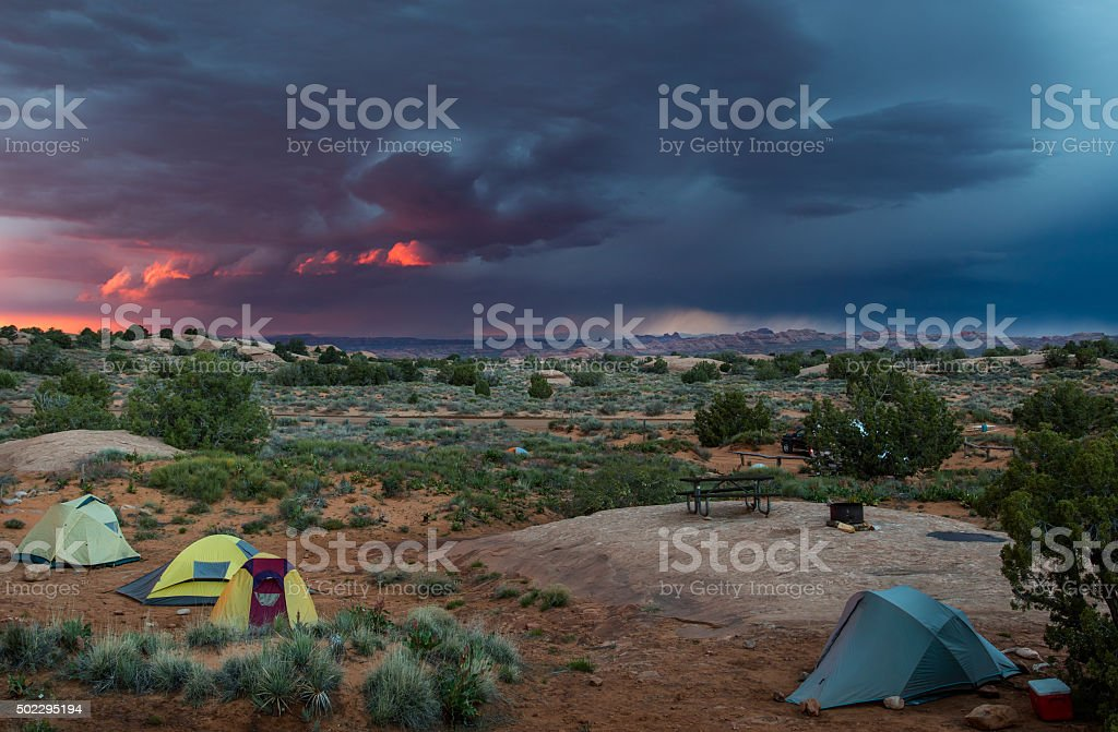 tents in desert with pink thunder storm sky stock photo
