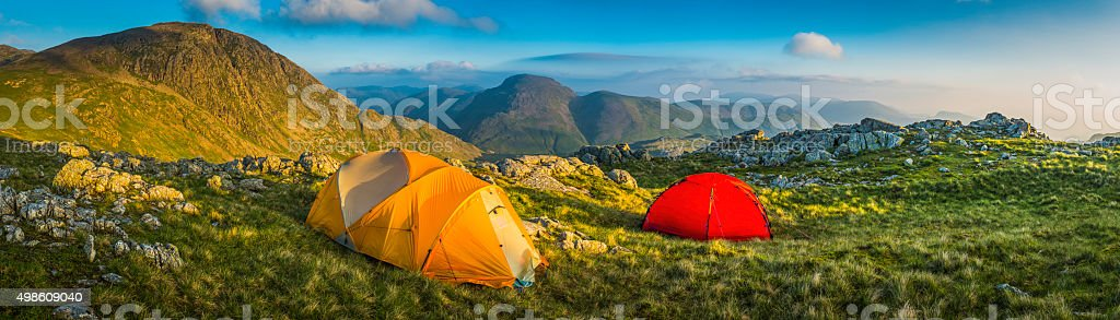 Tents wild camping on idyllic mountain summit panorama Lake District stock photo