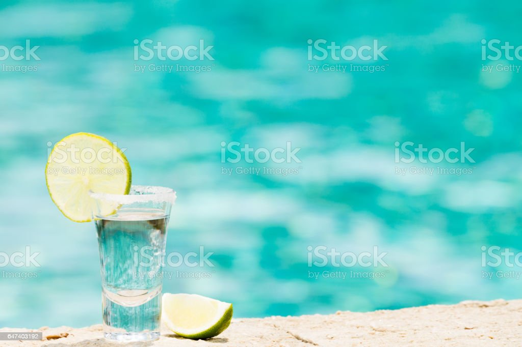 Tequila shot with lime on blue background stock photo