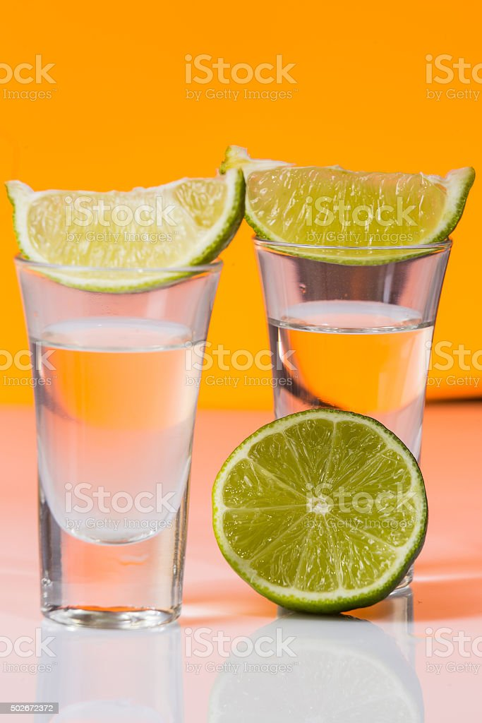 Tequila shot with of lime on the glass orange background stock photo