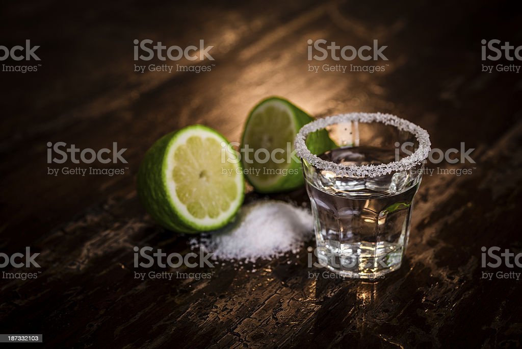 Tequila shot with salt and green lime stock photo