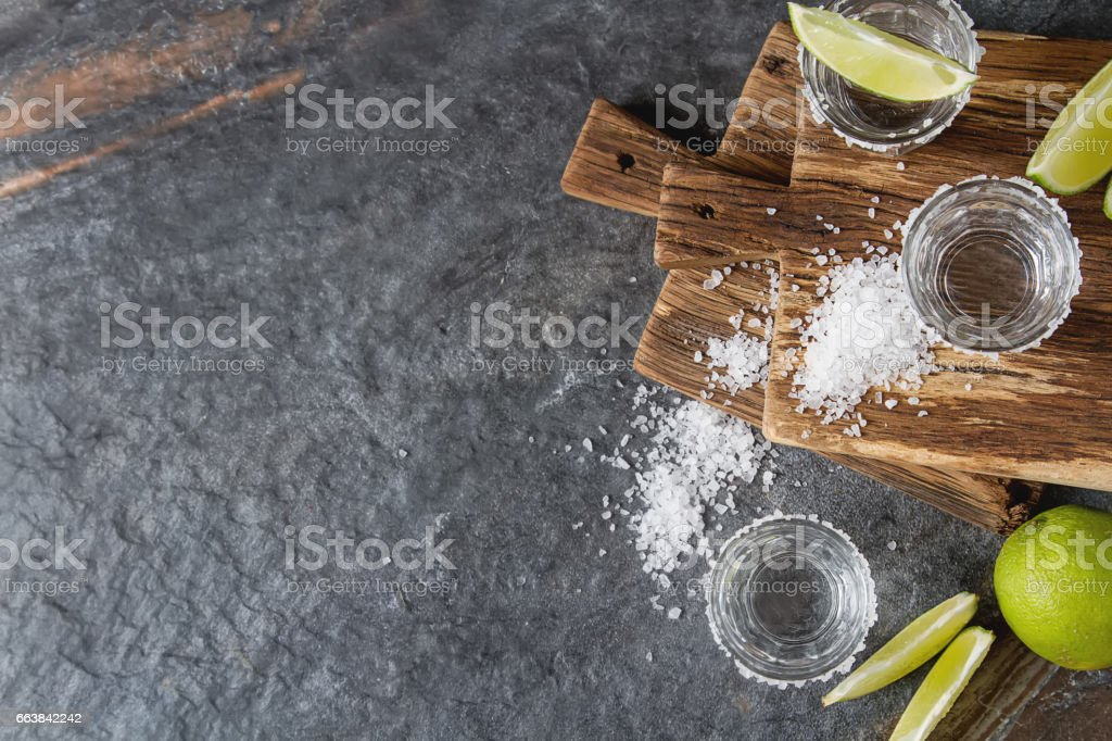 Tequila silver with lime and sea salt. Dark background. Selective focus stock photo