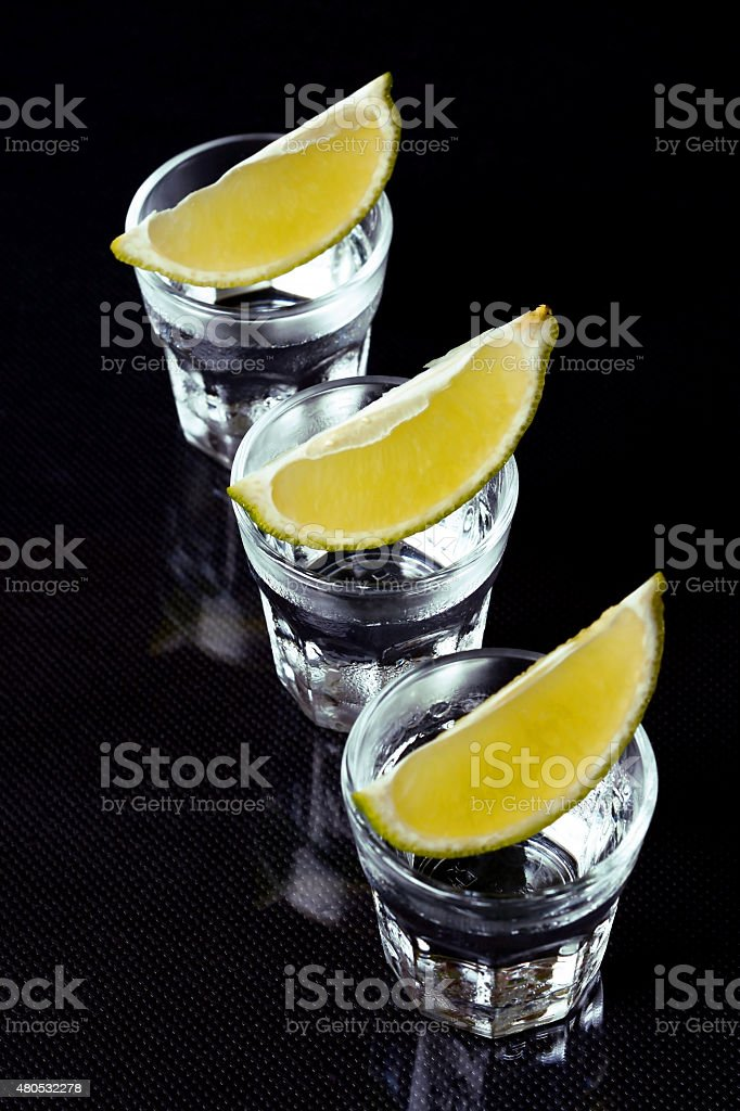 Tequila with lime on black background. stock photo