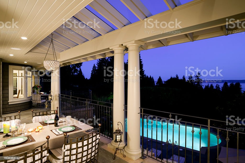 Terrace dinner with view of the pool in luxury home at dusk royalty-free stock photo