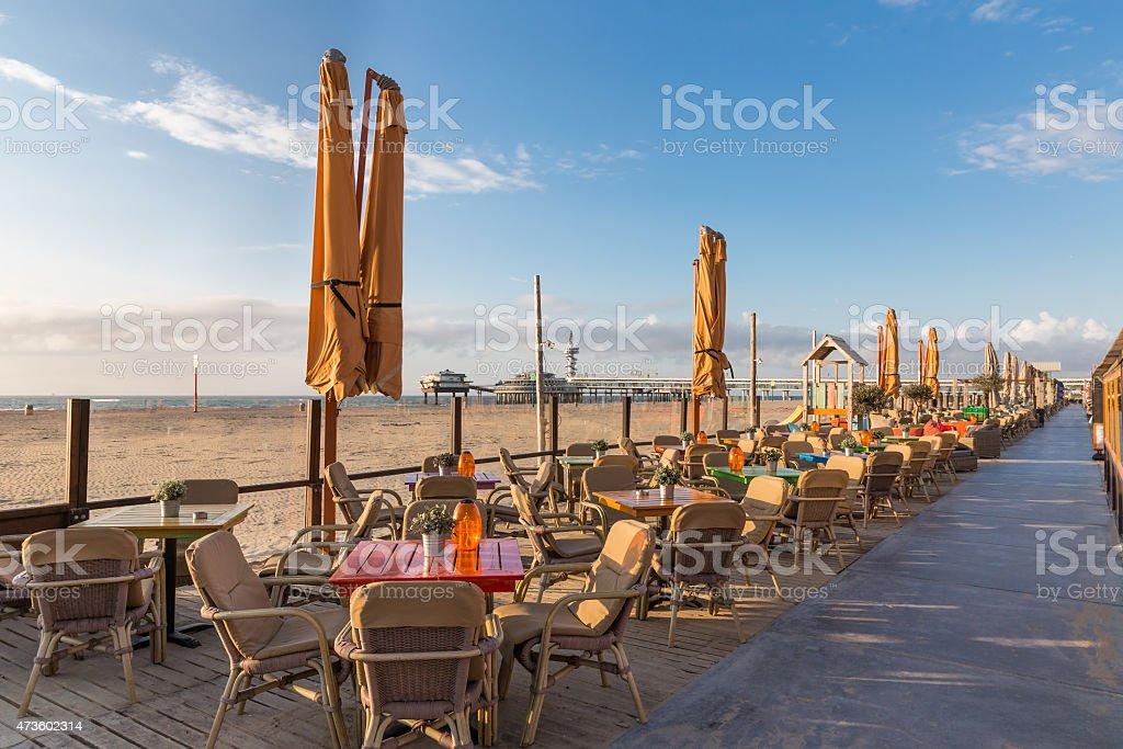 Terraces along Dutch beach with view at Pier of Scheveningen stock photo
