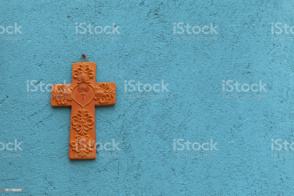 Terracotta cross on a turquoise wall stock photo