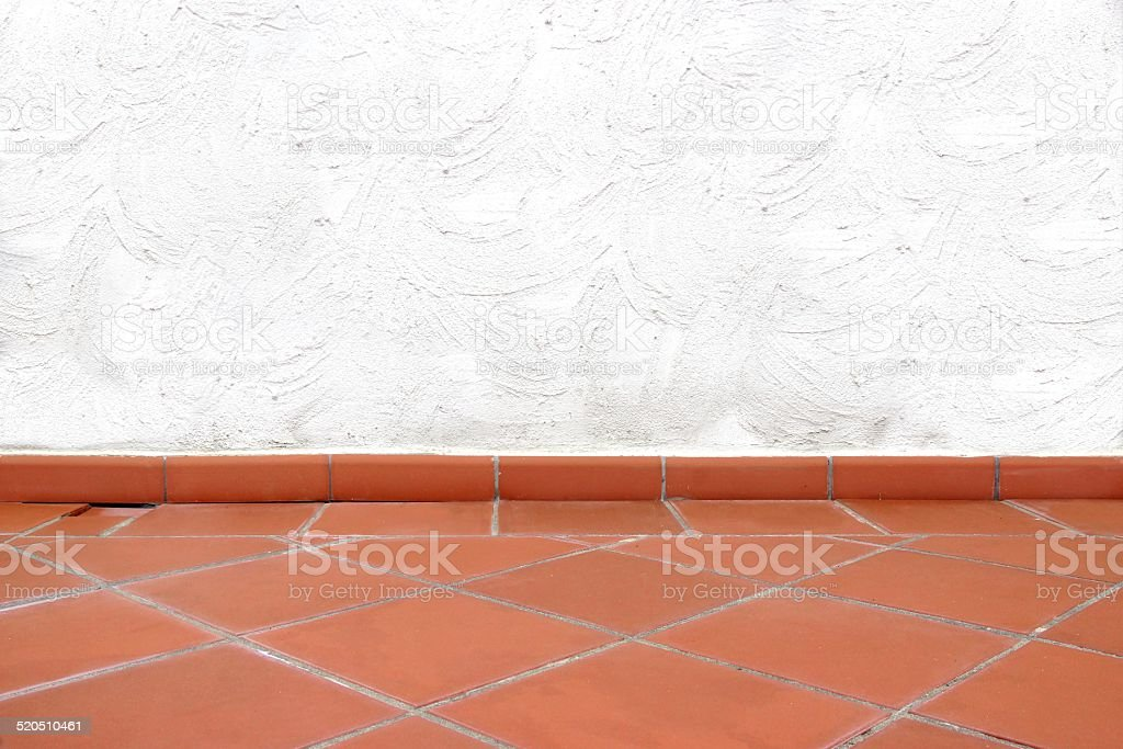 Terracotta Tailed Floor and White Concrete Wall stock photo