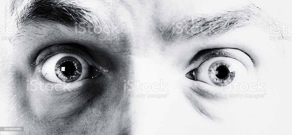 Terrified male eyes in black and white close up stock photo