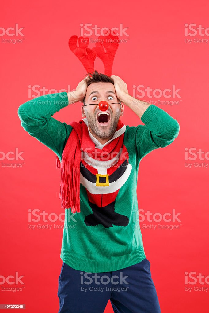 Terrified man in funny winter outfit against red background stock photo