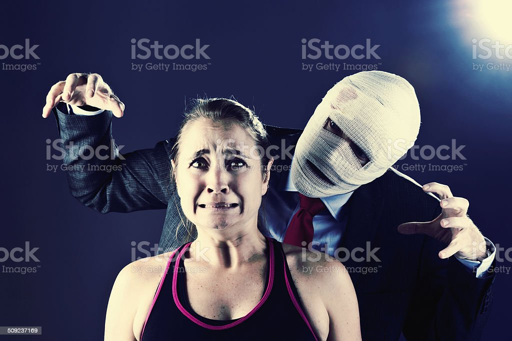 Terrified woman menaced by man disguised in bandages: Horror movie! stock photo