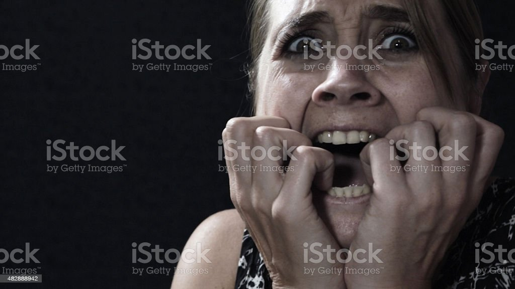 Terrified woman, wide-eyed, screaming, her hands to her mouth stock photo