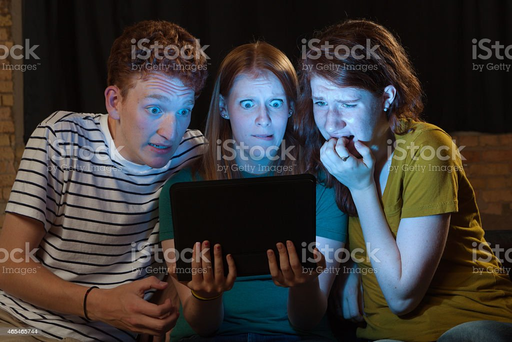 Terrified Young Adults Streaming Scary Movie on Digital Tablet Computer stock photo