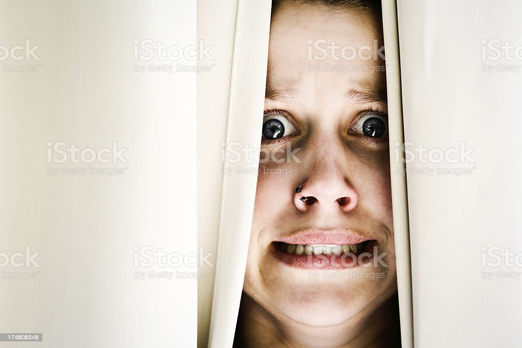 Terrified young brunette woman peeps through drapes, grimacing royalty-free stock photo