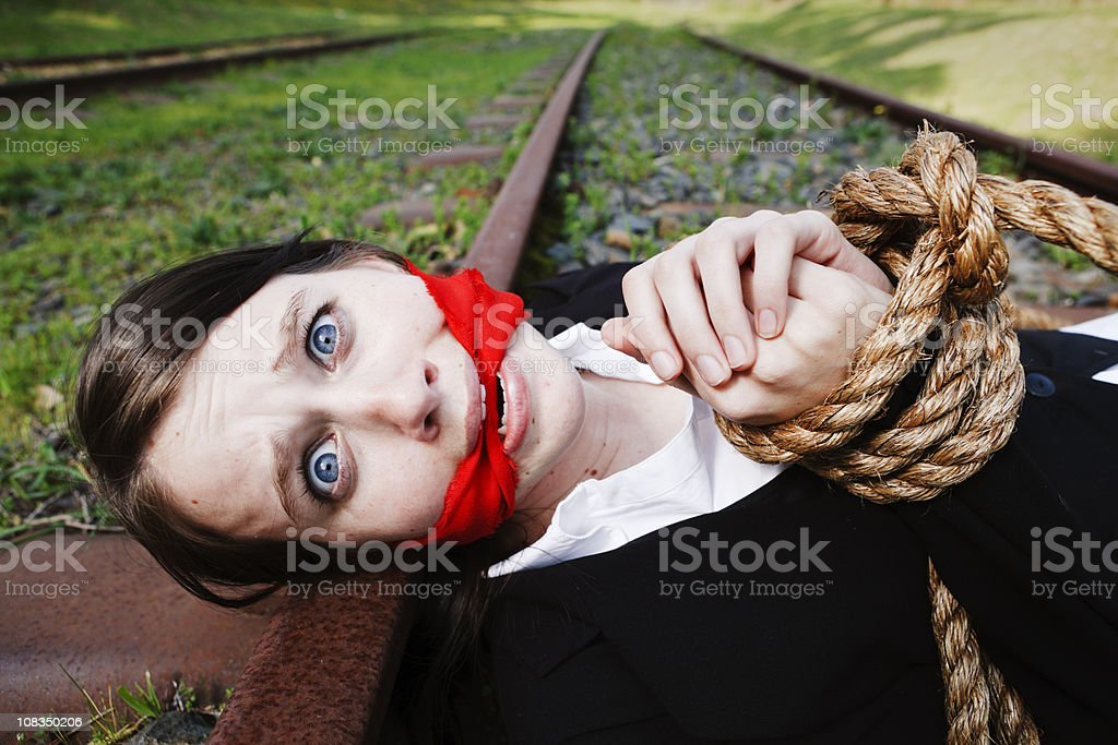 Terrified young woman, gagged and bound, lies on railway tracks royalty-free stock photo