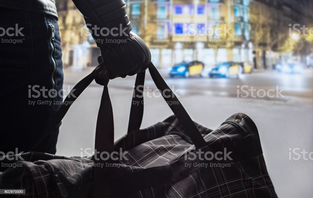 Terrorism and security threat concept. Terrorist at night. Suspicious man standing in city center holding black bag. Planning a bomb attack. Traffic, cars and buildings in the background. stock photo