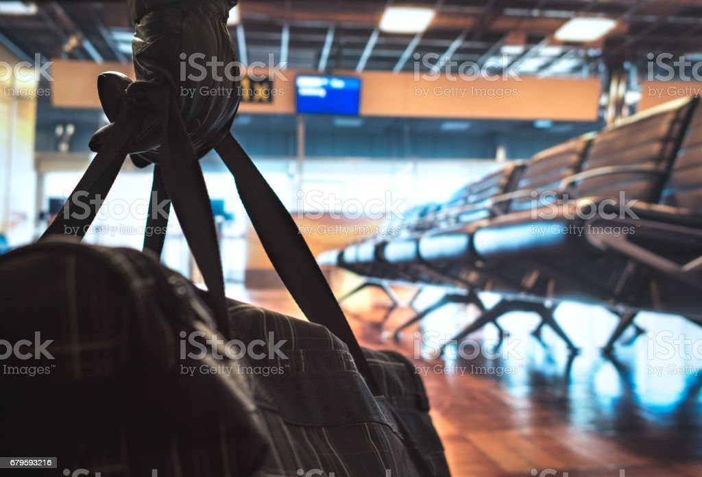 Terrorism in aiport. Dangerous terrorist planning a bomb attack in the waiting area and gate. Holding suspicious black bag with leather gloves. Anonymous criminal. Safety and security threat concept. stock photo