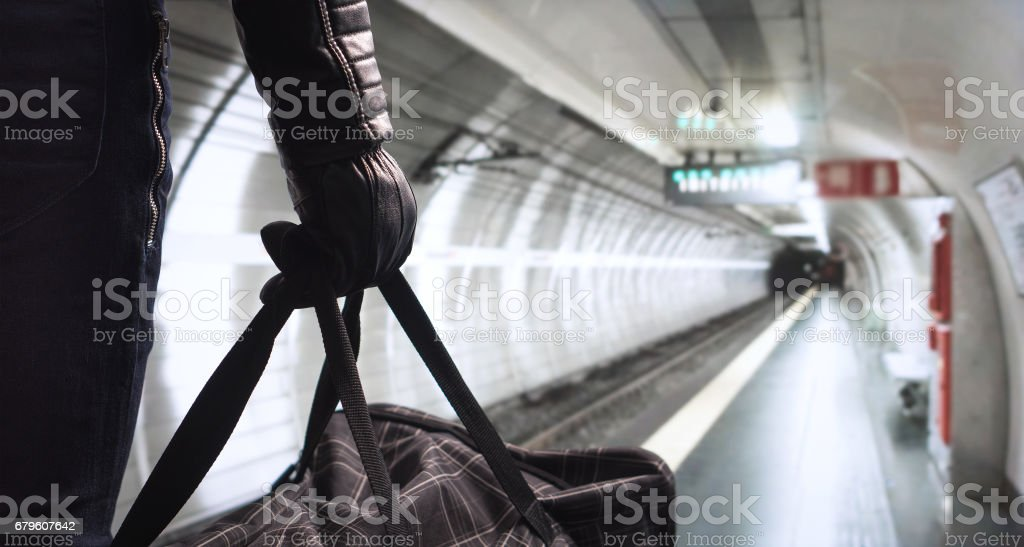 Terrorism in subway concept. Dangerous criminal with black bomb bag standing in underground station planning attack. Threatening man in the shadow with an evil plan . Terrorist in metro platform. stock photo