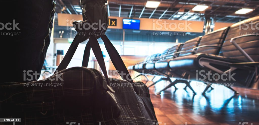 Terrorist in airport planning a bomb attack. Terrorism and security threat concept. Suspicious dangerous man in the shadows with black bag. Gate, bench and waiting area in the blurred background. stock photo