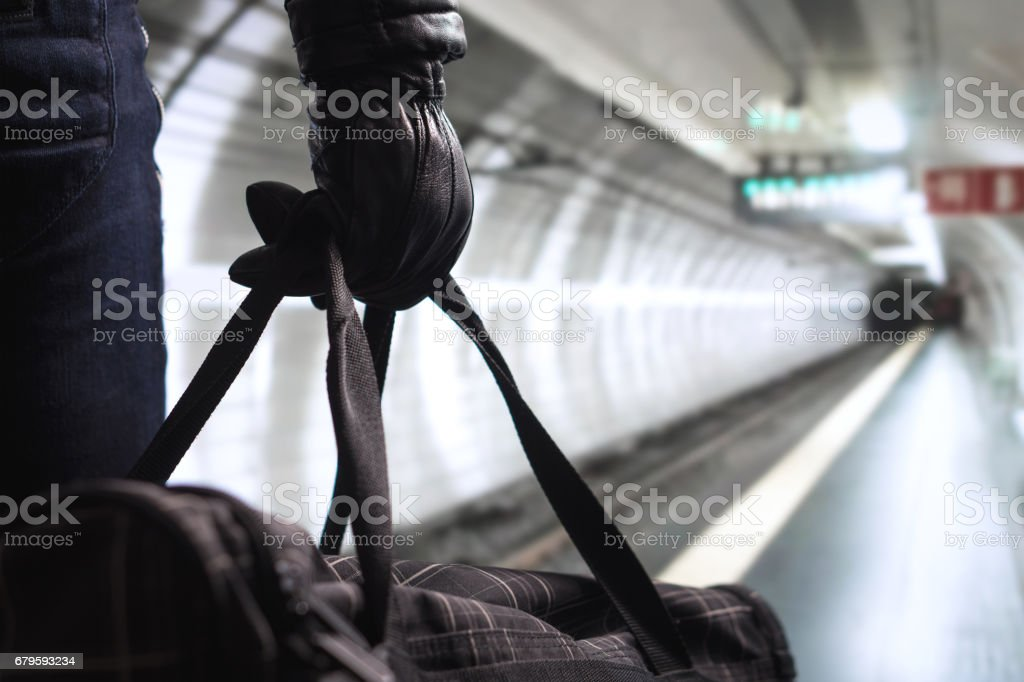 Terrorist in subway tunnel. Man planning bomb attack and strike in underground. Criminal standing in metro tunnel. Black bag and leather gloves. Security threat in public transportation concept. stock photo