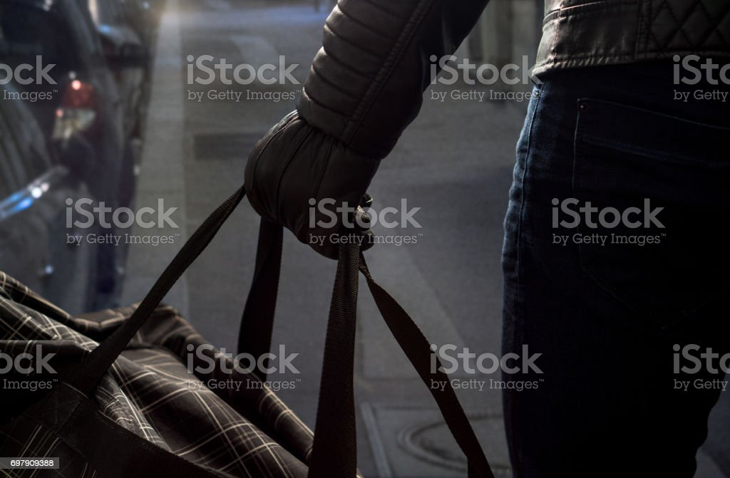 Terrorist standing in dark alley in the city center holding black bomb back with leather gloves. Suicide bomber in the shadows. Terrorism and security threat concept. stock photo
