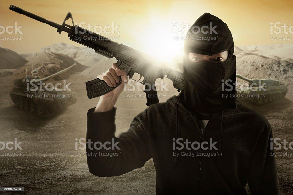 Terrorist with gun and military vehicle stock photo