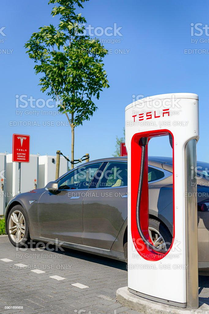 Tesla Model S electric car at a supercharger charging station stock photo