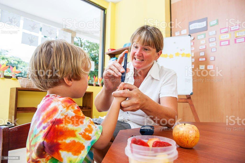 Testing blood sugar at school stock photo