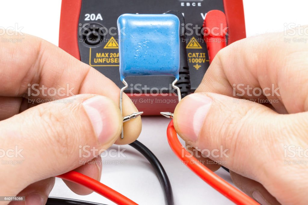 Testing capacitor with multimeter on a white background stock photo