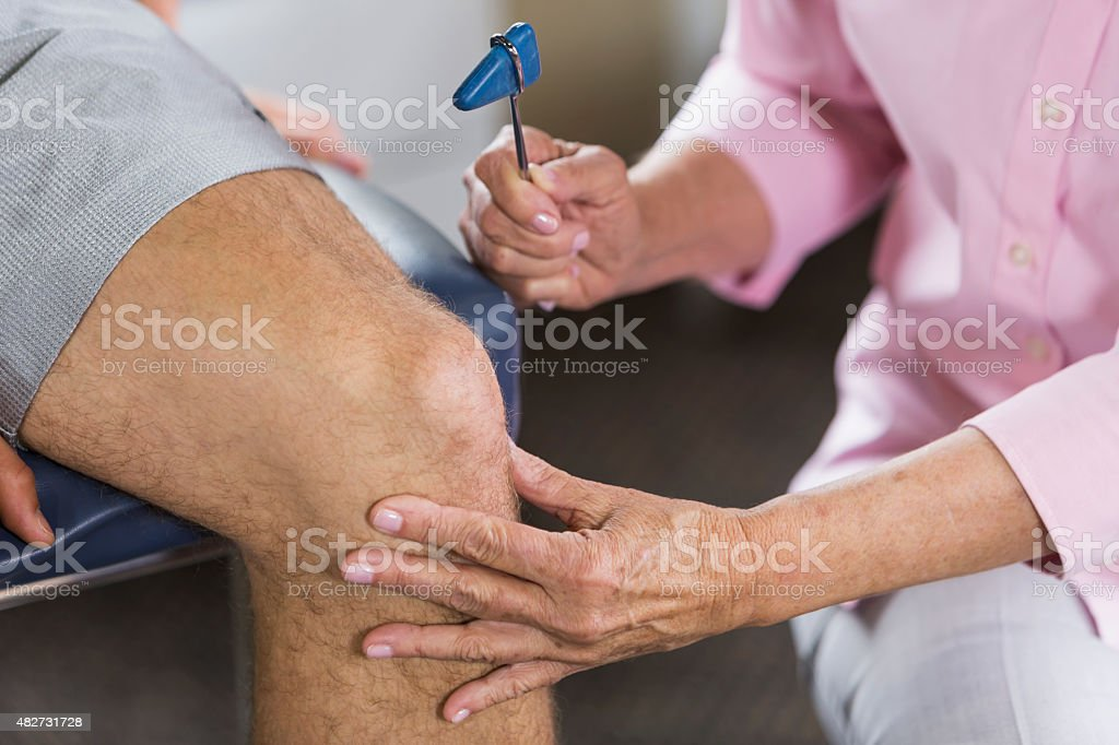Testing reflexes with reflex hammer stock photo