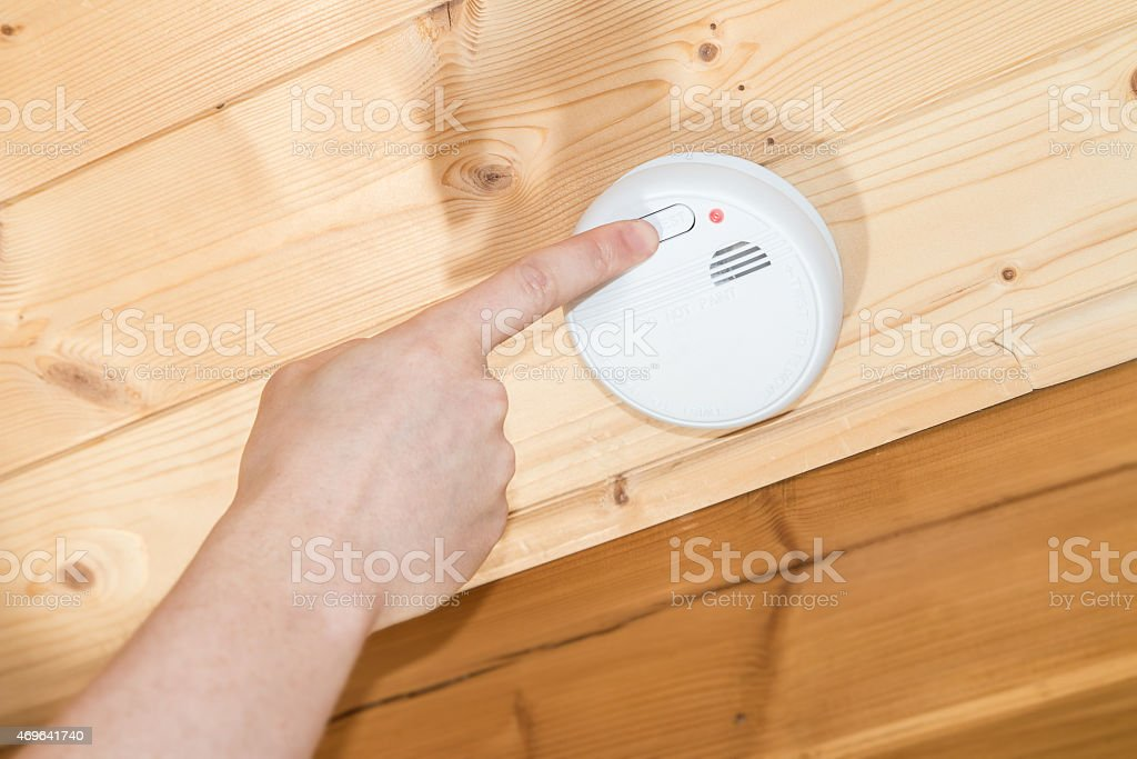 Testing wood ceiling mounted common white home smoke detector alarm stock photo