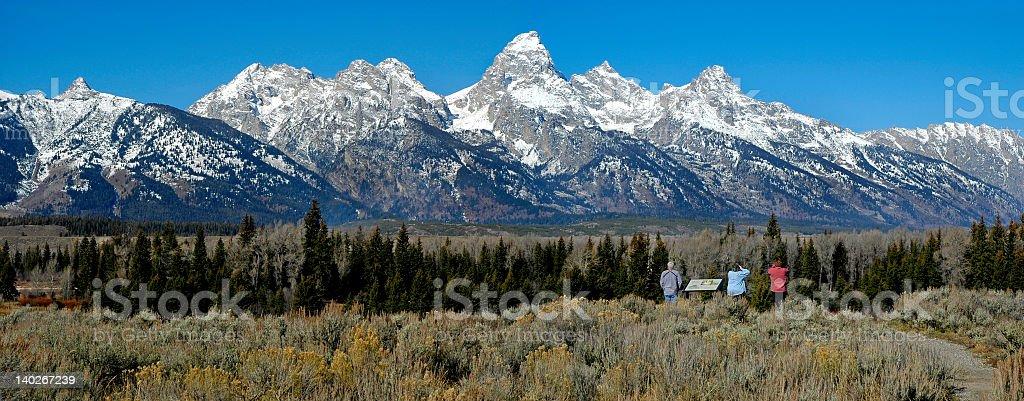 Teton mountain range panorama with three tourists royalty-free stock photo