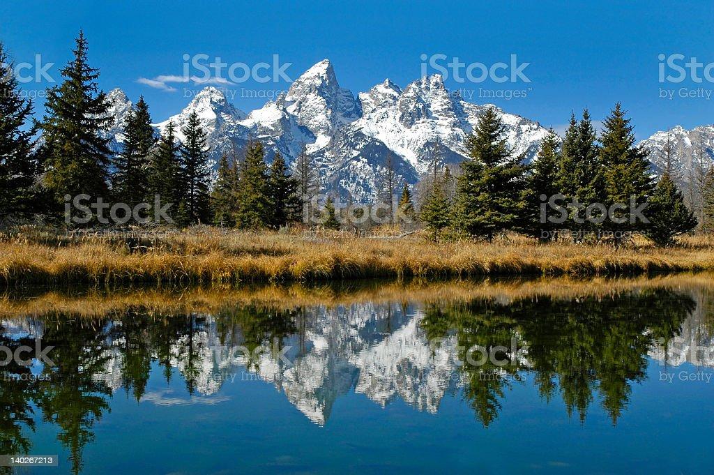 Teton mountain range reflecting in river water stock photo
