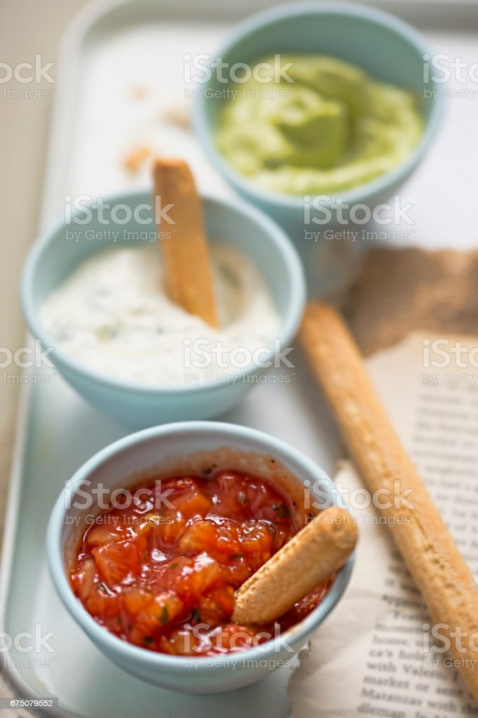 Tex mex - salsa, sour cream with chives and avocado dips served with bread sticks stock photo