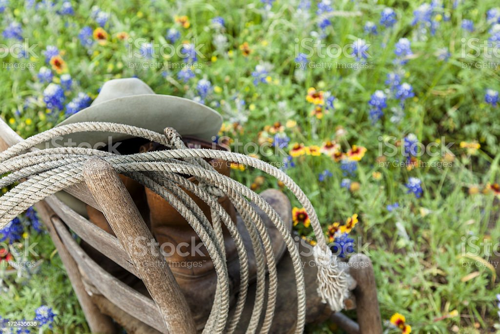 Texas Bluebonnets:  Old wooden chair, rope, hat, boots and bluebonnets. royalty-free stock photo