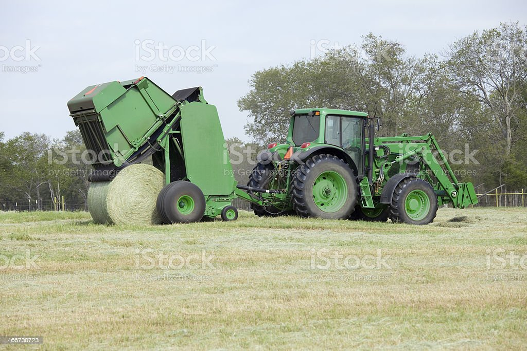 Texas farmer using hay baler and tractor royalty-free stock photo