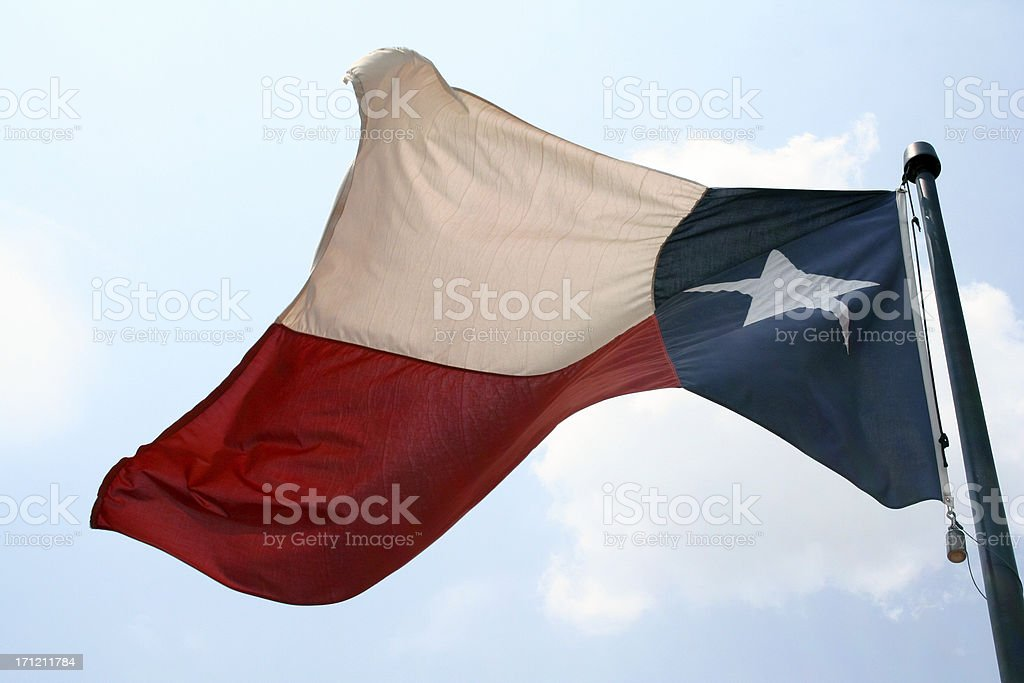 Texas Flag Waving In The Wind Of Bright Blue Sky royalty-free stock photo