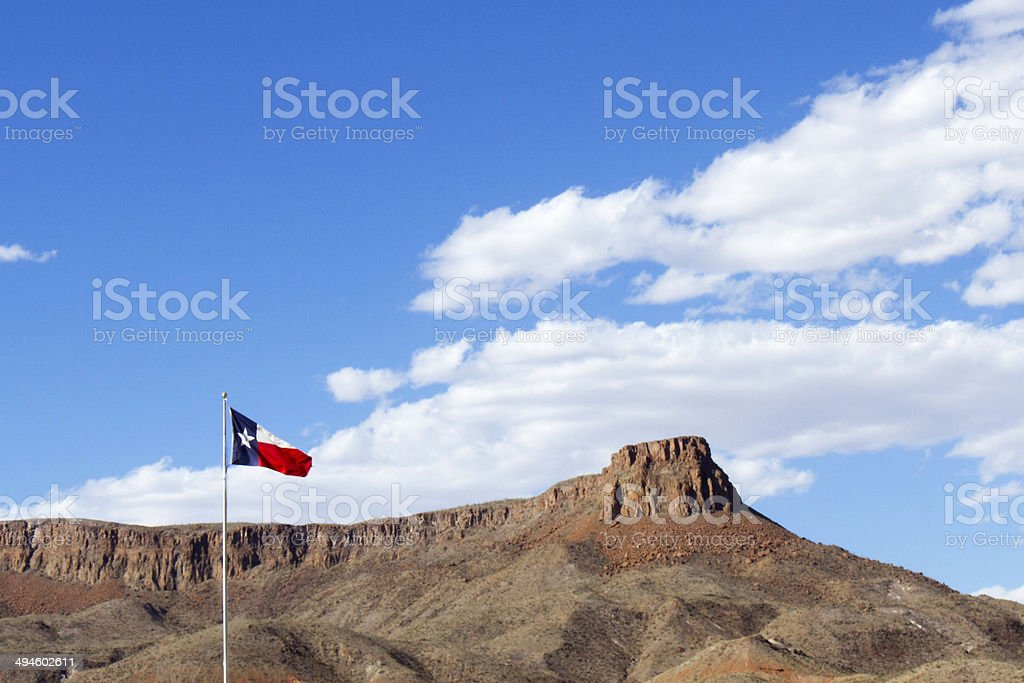 Texas State Flag with Blue Sky and Rock Mesa stock photo