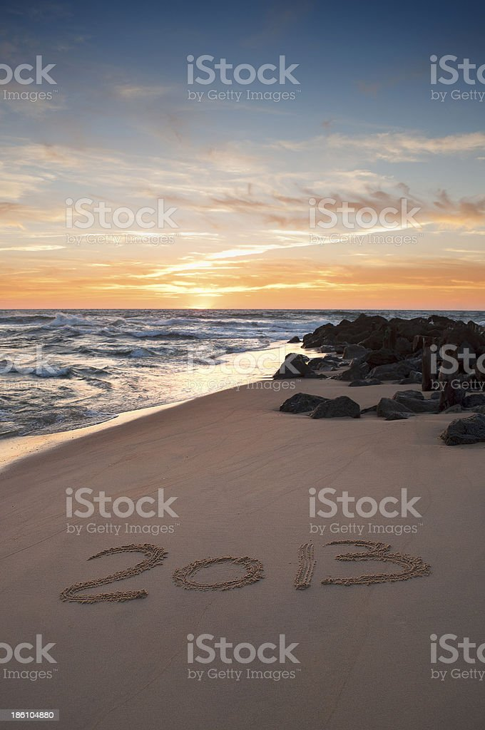 Text 2013 writen on the sand at sunset stock photo