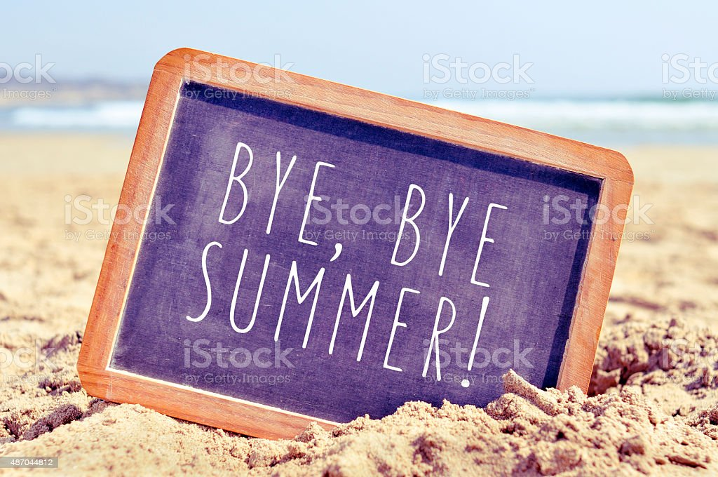 text bye, bye summer in a chalkboard on the beach stock photo