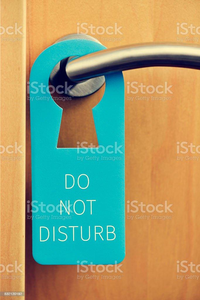 text do not disturb in a door hanger stock photo