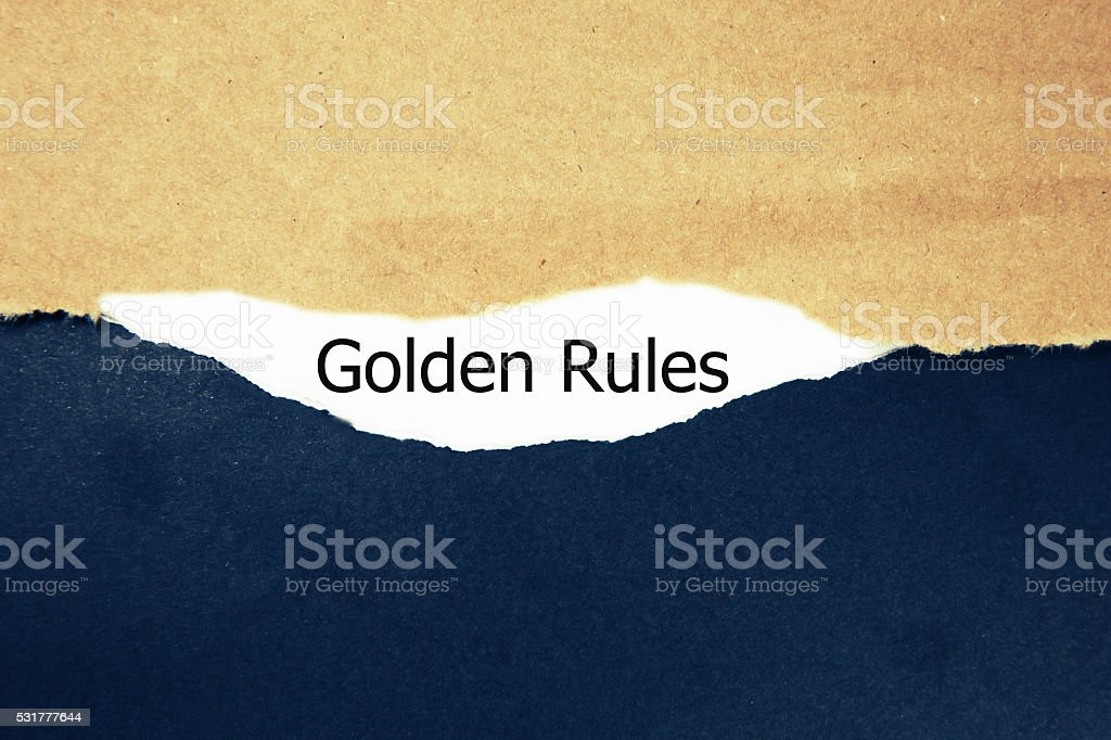 Text 'golden rules' appears under the torn paper. stock photo