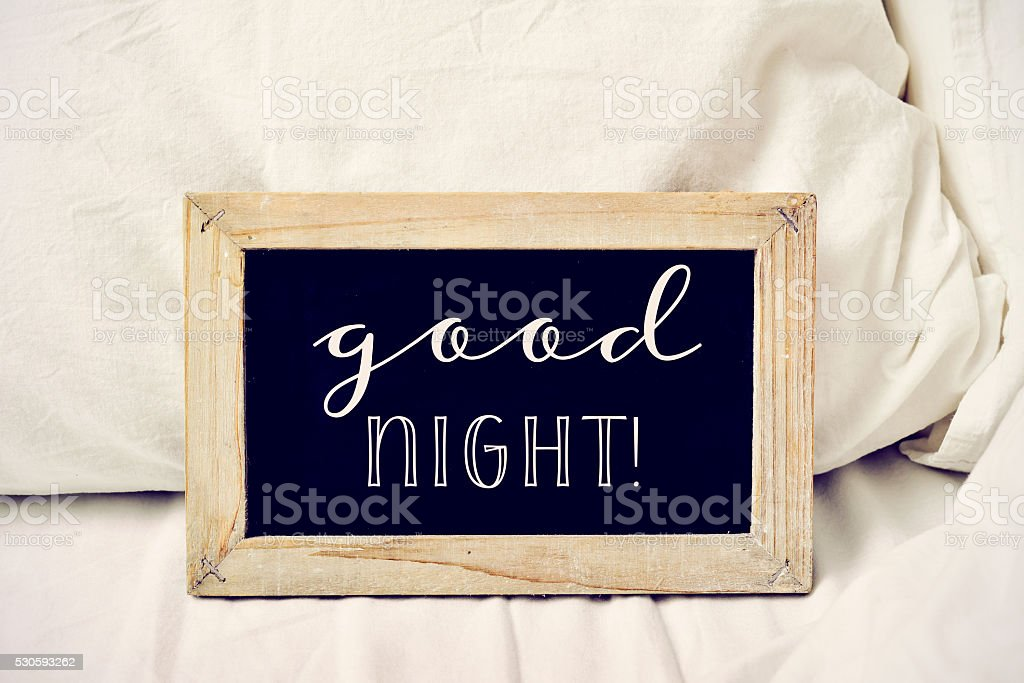 text good night in a chalkboard on a bed stock photo