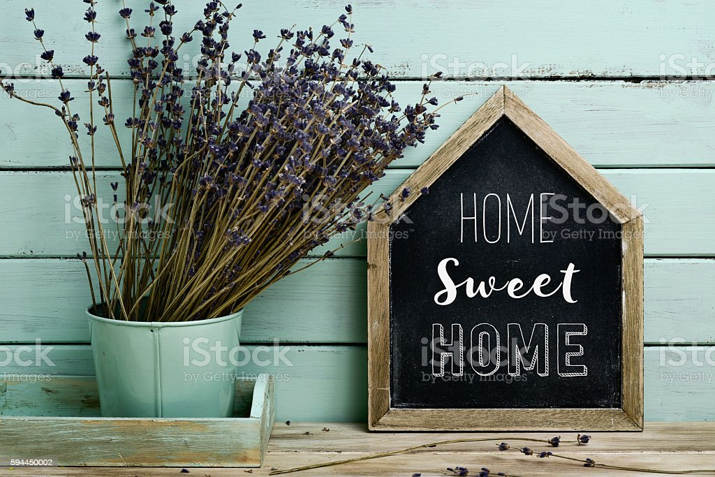 text home sweet home in a house-shaped signboard stock photo