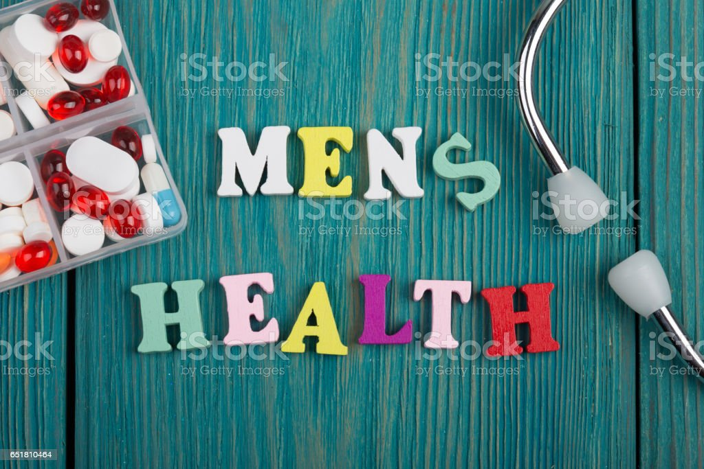 Text 'Men's health' of colored wooden letters, stethoscope and pills stock photo