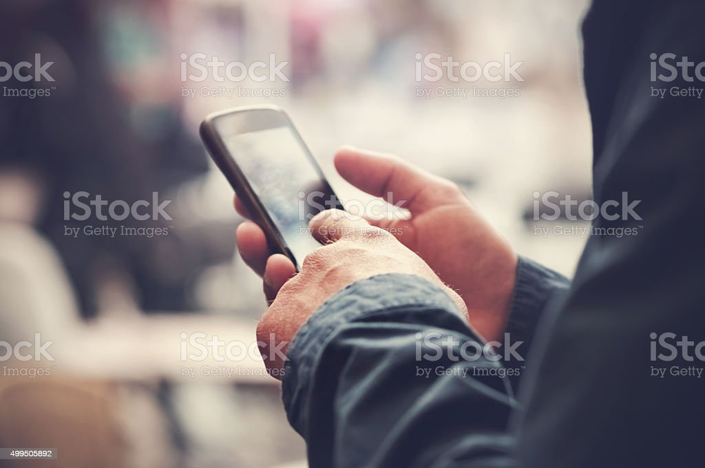 Text messaging smartphone in an urban environment. stock photo