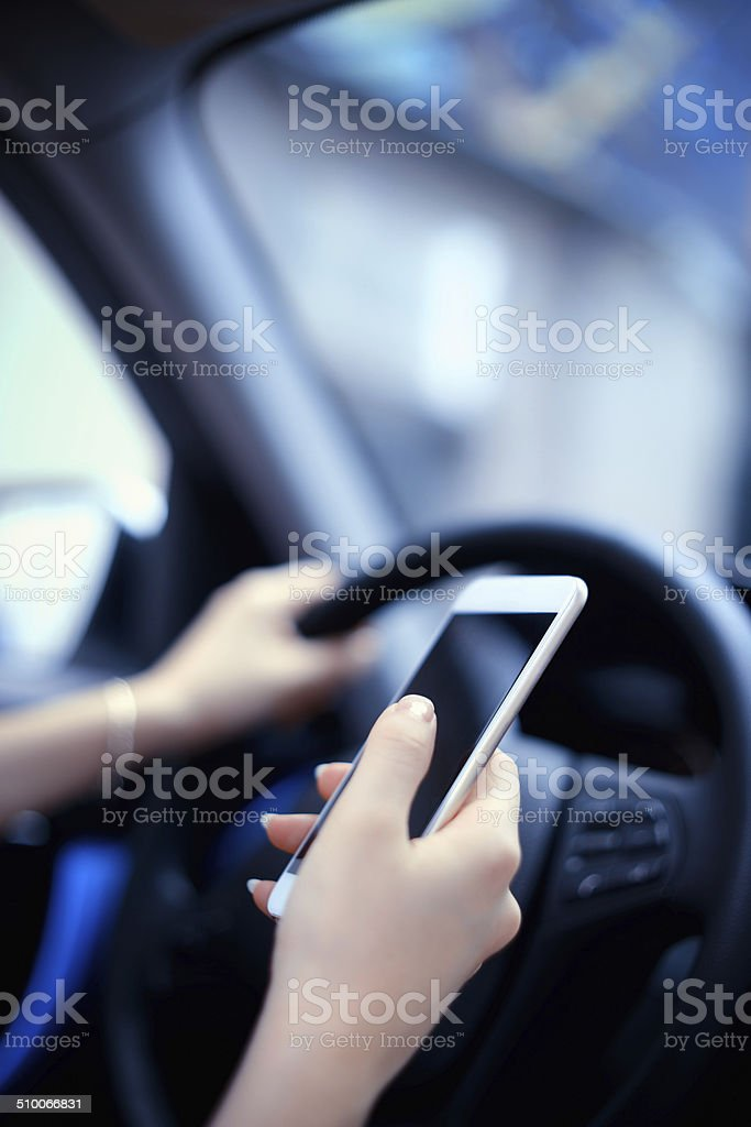 Text messaging smartphone while driving stock photo