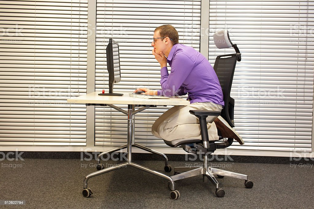 text neck - man in slouching position kneeling on  chair stock photo