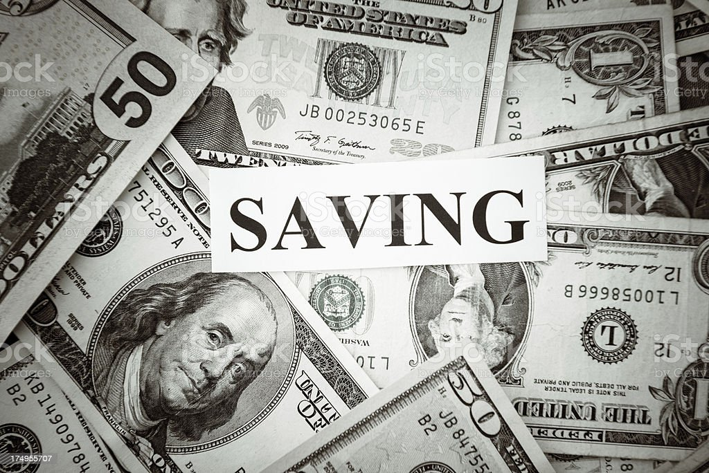 SAVING text on a bunch of American dollars stock photo
