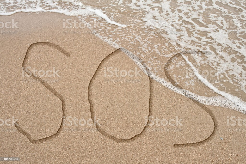 SOS Text on sand and wave royalty-free stock photo