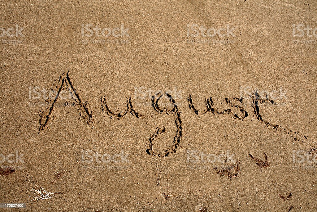 Text on the sand that says August royalty-free stock photo
